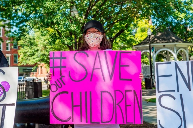 """Demonstrators in Keene, New Hampshire, gather at a """"Save the Children Rally"""" to protest child sex trafficking and pedophilia around the world, on September 19, 2020. - Anti-paedophilia protests are flaring in th US where the QAnon movement started. QAnon is the umbrella term for a sprawling set of internet conspiracy theories that allege that the world is run by a cabal of Satan-worshiping pedophiles who are plotting against US President Donald Trump while operating a global child sex-trafficking ring. (Photo by Joseph Prezioso / AFP) (Photo by JOSEPH PREZIOSO/AFP via Getty Images)"""
